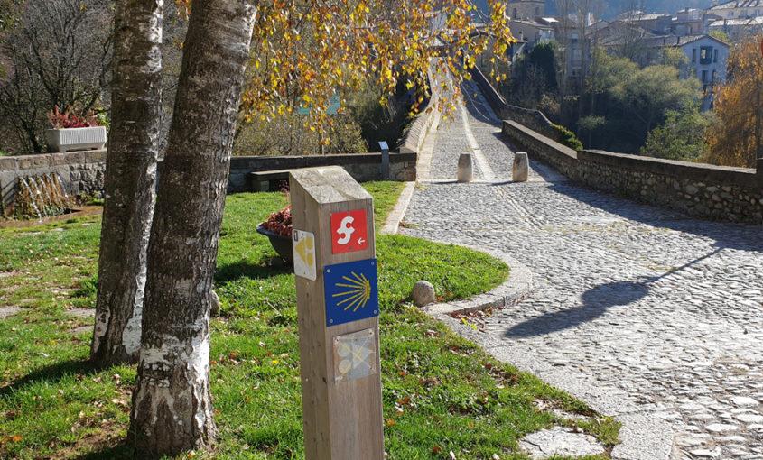 Imatge d'una estaca amb indicadors de senderisme davant la rampa del pont de Sant Joan de les Abadesses