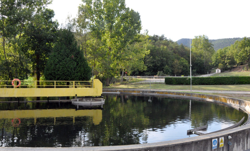 Imatge d'un decantador de la depuradora de Ripoll i Campdevànol, amb arbres de fons reflectits a l'aigua