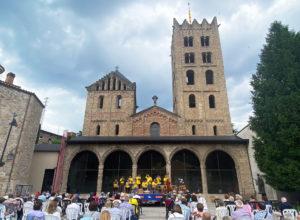 El públic, assegut mirant la cobla, amb el monestir de Ripoll al fons, durant la Trobada sardanista del Ripollès 2021