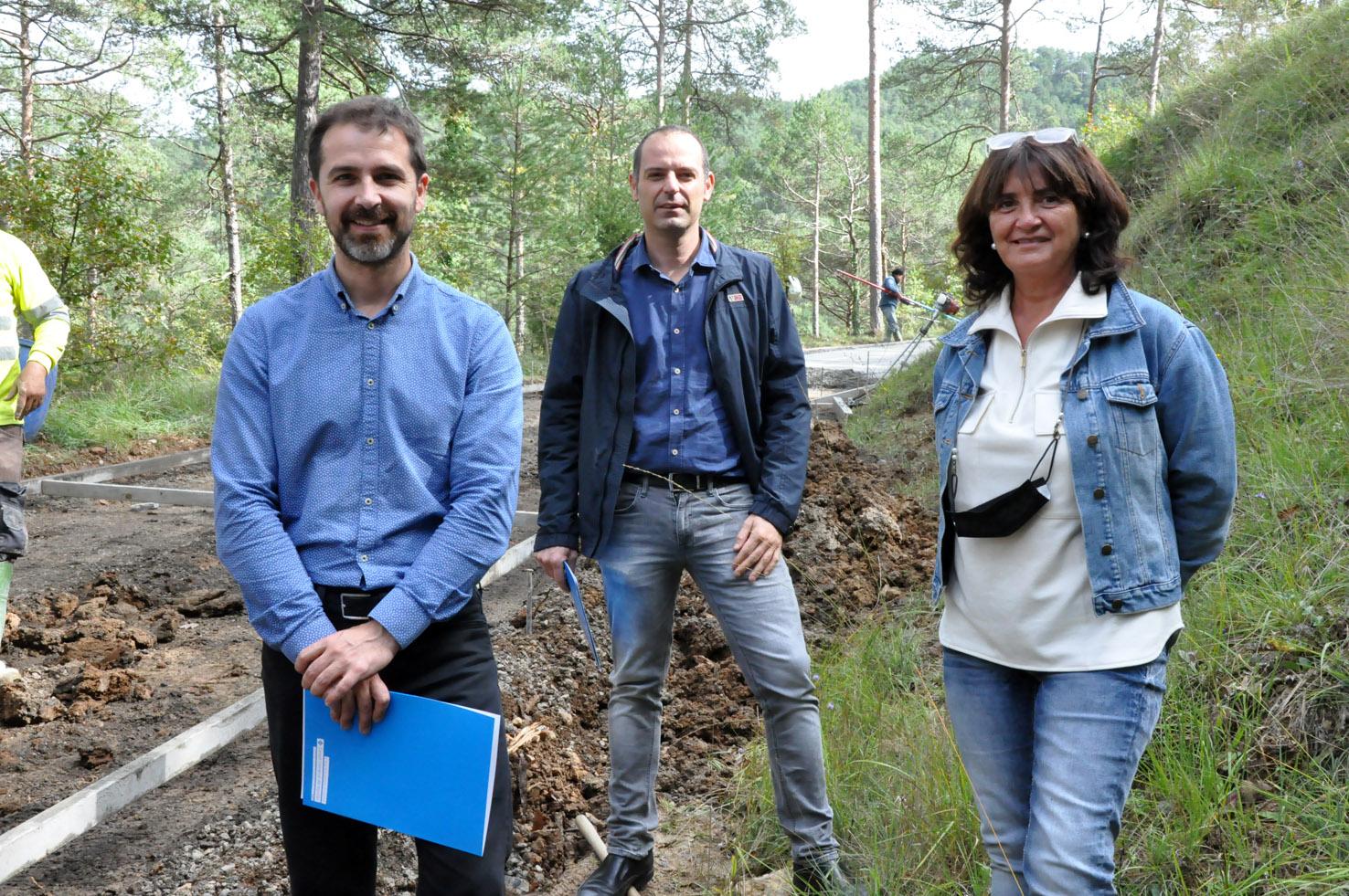 Joaquim Colomer, Enric Pérez i Dolors Costa, davant les màquines que pavimenten el camí d'Estiula, a Campdevànol