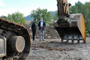 El president, Joaquim Colomer, i l'alcalde de Sant Joan de les Abadesses, Ramon Roqué, al costat d'una excavadora, a les obres del paratge de les Cinc fonts